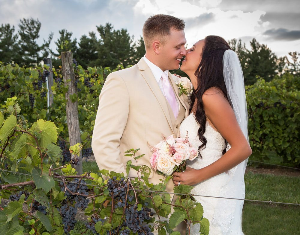 Bride and groom kiss next to vineyard grapes