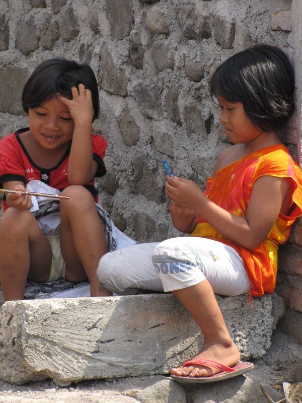 Passing out pencils to some  children in the local village