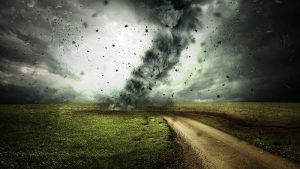 image shows a tornado tearing down a road