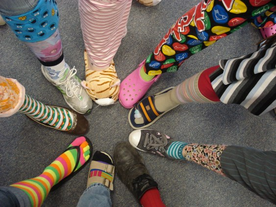 group of people each with one foot in a circle showing off their colorful socks and shoes