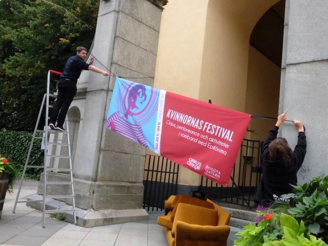 Carl Fristedt och Eva Lundgren Stenbom hänger upp Festivalbanderollen