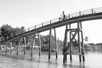 Frau auf Fahrrad auf Brücke über Kanal