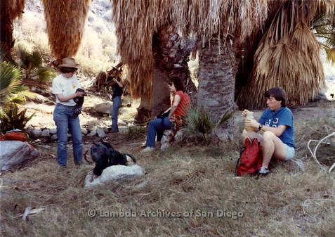 P008.092m.r.t Laguna Mountains 1984: Group sitting below palm trees for lunch break