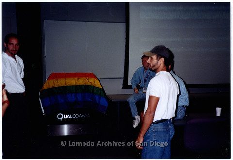 P201.027m.r.t National Coming Out Day at Qualcomm: Four people standing in Q Auditorium near projection screen
