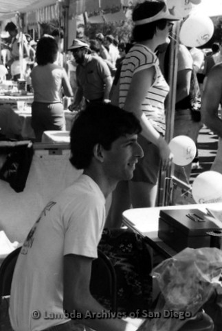 San Diego Lambda Pride Festival: John J. Ciaccio (center) (b.1958 - d.1985) sitting at the Gayzette Newspaper Booth with Christine Kehoe standing in background.