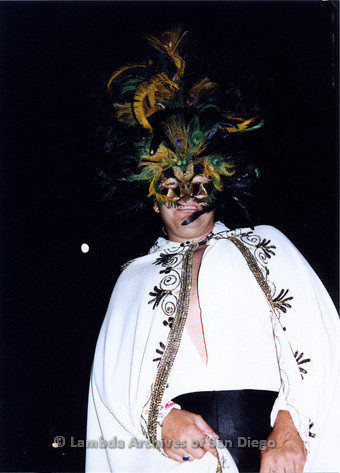 P184.001m.r.t Nightmare On Normal Street: Man dressed in white cape and mardi gras feather mask.