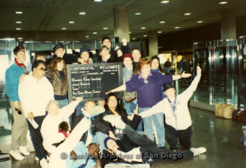 """""""The Magic Music Makes"""" San Diego Women's Chorus (SDWC) first choral festival with Sister Singers 1991: San Diego Women's Chorus posing in front of a welcome sign at airport, including Conductor, Cynthia Lawrence Wallace (standing far left) and wife Peggy"""