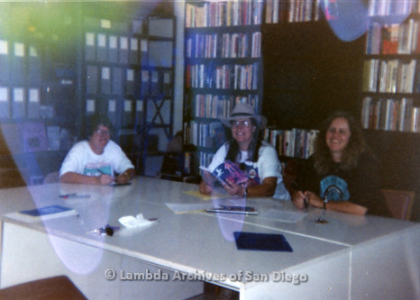 P199.010m.r.t (L to R) Anonymous woman, Laura Opfer, and Debbie Zeyher sitting at table inside Lambda Archives