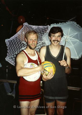 P099.071m.r.t Halloween: Two men in retro swim suits holding umbrellas and beach balls