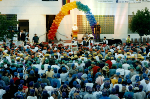 P234.039m.r.t SD Pride Rally: Man on stage speaking in front of people in colored hats that make rainbow in front of Normal Street Center