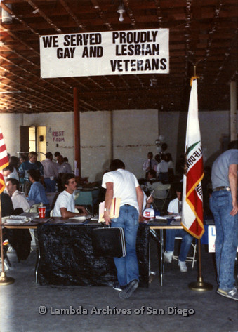 "P022.015m.r.t The Center, Normal Street: People visiting booth with banner overhead: ""WE SERVED PROUDLY GAY AND LESBIAN VETERANS"""