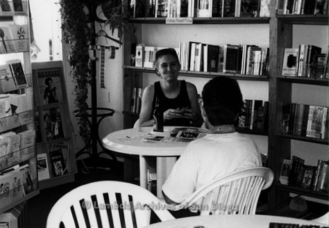 P167.101m.r.t Paradigm Women's Bookstore: Two women inside bookstore sitting and eating at table