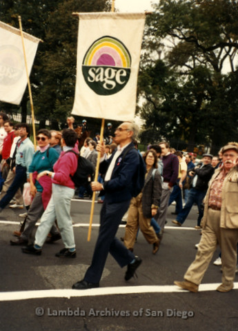 """P019.282m.r.t Second March on Washington 1987: People marching on street, man holding sign that reads: """"sage"""""""