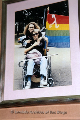 P119.055m.r.t LASD City Hall Exhibit 2010: A framed photo of Kate Johnson and a woman in a wheelchair carrying a rainbow flag with lambda symbol