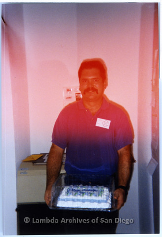 P200.006m.r.t Lesbian and Gay Historical Society of San Diego Event: Volunteer, Jim Burnett holding a cake at the archives