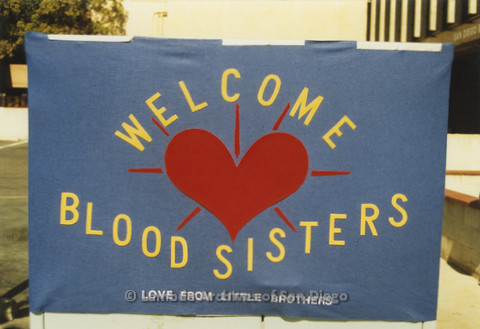"P019.078m.r.t AIDS Quilt at San Diego Golden Hall 1988: Close up of ""Welcome Blood Sisters Love from Little Brothers"" banner"