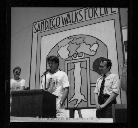 P116.114.08m.r.t San Diego Walks for Life 1987: Gordon Thomson speaking at podium with Nicole Murray Ramirez to the right and unknown man to left