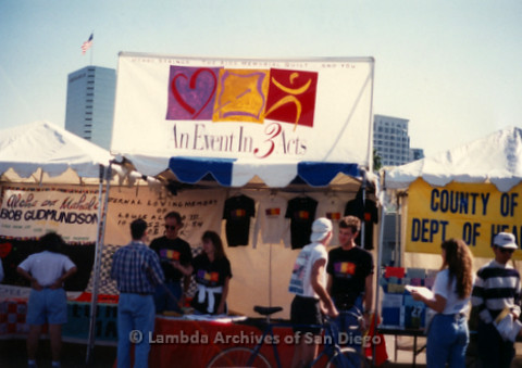 """P197.023m.r.t AIDS Walk San Diego 1991: Organizations tabling in parking lot. One sign reads: """"An Event in 3 Acts"""""""