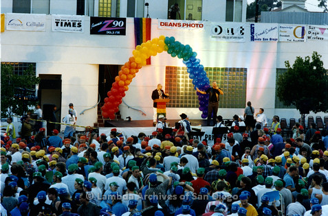 P234.041m.r.t SD Pride Rally: People creating rainbow with colored in front of Normal Street Center, speaker on stage