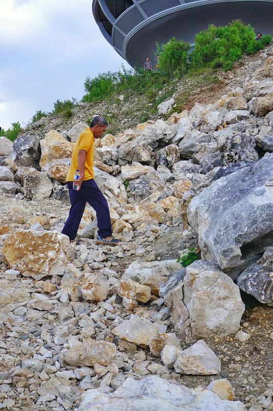 Pak Naja, tour guide kami, sedang melangkah menuju pelataran Patung Yesus.