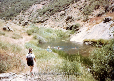 P008.037m.r.t Harvey Moore Trail 1983: Mary Revere walking towards swimmers in the creek