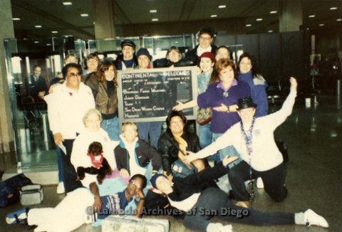 """The Magic Music Makes"" San Diego Women's Chorus (SDWC) first choral festival with Sister Singers 1991: San Diego Women's Chorus posing in front of a welcome sign at airport, including Cynthia Lawrence Wallace and Peggy Heathers (far left), Judy Reif (far"