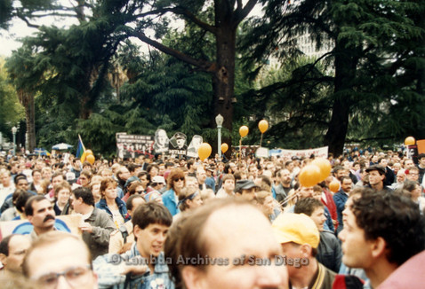 P019.138m.r.t March on Sacramento 1988 / Pre Parade gathering: Large crowd of people with signs and balloons