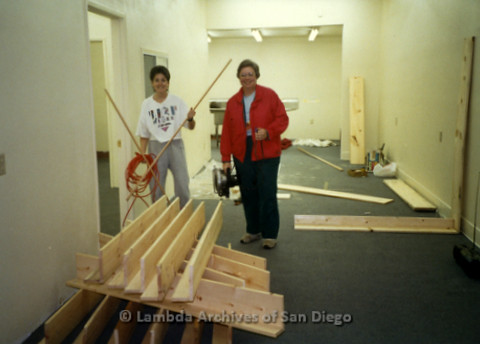 P169.030m.r.t Paradigm Women's Bookstore - Moving in: Two women standing in a room with a pile of wooden shelves
