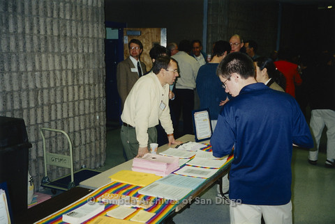 "P122.014m.r.t Youth Speak to GLSEN ""II"": Attendees walking past resource table with rainbow runner"