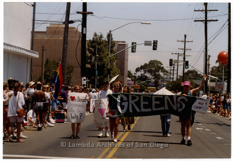 """P201.010m.r.t San Diego Pride Parade 1992: Group of people walking marching with signs, including one that reads: """"Greens"""""""