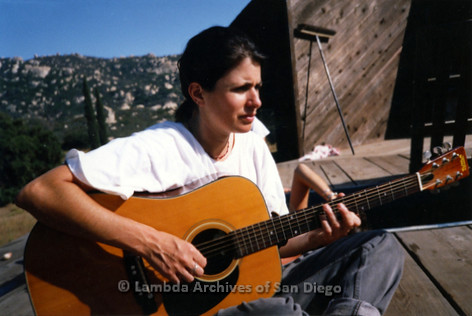 1994 - Photo shoot in Dulzura, CA: Zanne playing acoustic guitar with mountains in the background.