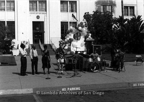 P116.022m.r.t San Diego Walks For Life 1986: Band performing in front of County of San Diego building in front of a small stage and podium