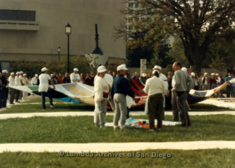 P019.302m.r.t AIDS Memorial Quilt 1987: Group of people positioning large section of AIDS Memorial Quilt on lawn