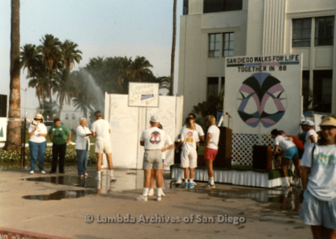 """P197.010m.r.t San Diego Walks For Life 1988: People gathered near stage in front of signs that read: """"San Diego Walks For Life-Together in '88"""" and """"Express Yourself"""""""