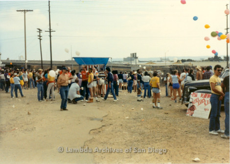 1982 - San Diego Lambda Pride Festival, Crowd of people in dirt parking lot area.