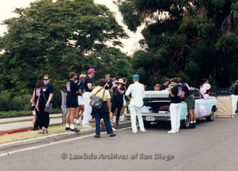 P119.025m.r.t San Diego Pride: Lambda Archives members wait by a car, including Doug Moore (pink hat)