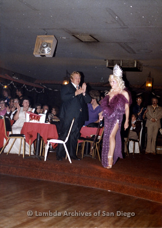 1983 - Imperial Court de San Diego Coronation Ball: Golden Empress XI of San Diego Nicole Murray Ramirez performing during Coronation wearing a feathered purple gown and crown, standing with Crown Prince IV Leon .