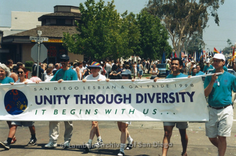 San Diego LGBTQ Pride Parade, July 1998: Judi Schaim (far left), Joe Mayer (3rd left), Sheila Clark (rainbow hat), Judy Reif (3rd right) with other Pride Board members carrying the 1998 theme banner 'Unity Through Diversity, It Begins With Us...'