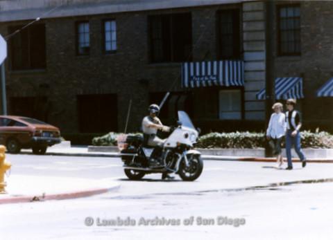 San Diego Lambda Pride Parade: Motorcycle Police officer waits at crosswalk while Parade Crowd Cross the Street.