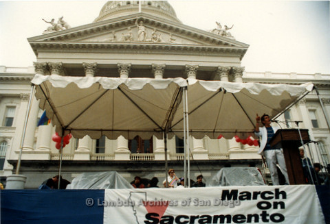 P019.137m.r.t March on Sacramento 1988 / Pre Parade gathering: Man speaking on stage in front of City Hall
