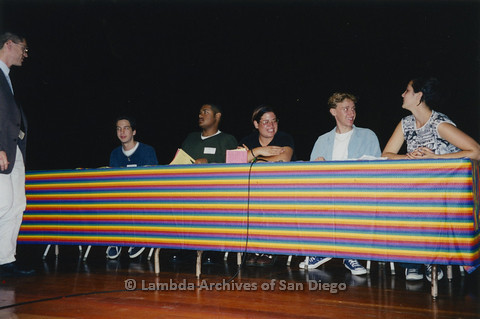 "P122.016m.r.t Youth Speak to GLSEN ""II"": Youth sitting on stage, behind table with rainbow cloth"