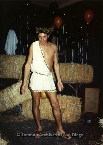 P099.067m.r.t Halloween: A man in a toga in front of hay bales and Halloween balloons