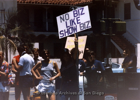 San Diego Lambda Pride Parade: Crowd holding Pro-LGBT signs across the street from Fundamentalist Christian Protesters. Person Holding Sign Reading 'No Biz Like Show Biz.