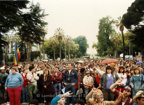 P019.171m.r.t March on Sacramento 1988 / Pre Parade gathering: Large crowd of people standing behind rope barrier
