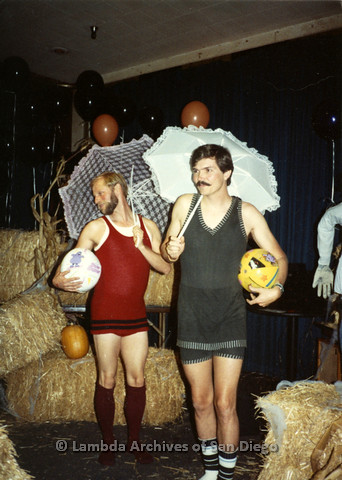 P099.057m.r.t Halloween: Two men in retro bathing suits, holding umbrellas and beach balls