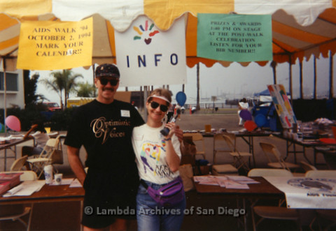 P197.031m.r.t AIDS Walk San Diego 1993: Sharon Parker and Patrick Stevens in front of AIDS Foundation San Diego booth, Sharon holding a phone