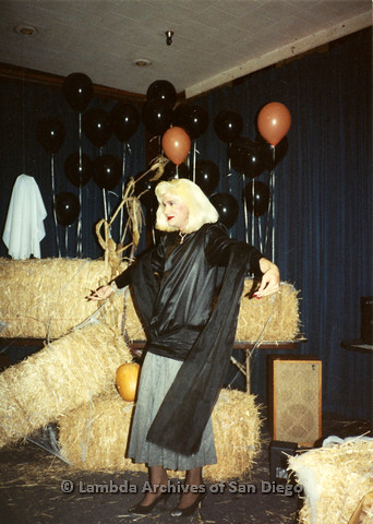 P099.082m.r.t Halloween: A man in black and grey women's clothing with blond wig, in front of hay bales and balloons