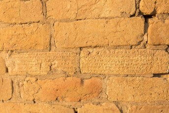 Na drieduizend jaar zien de bakstenen er nog pico bello uit, maar het spijkerschrift op ooghoogte aan de basis verraad dat het nog de originele bakstenen zijn.
