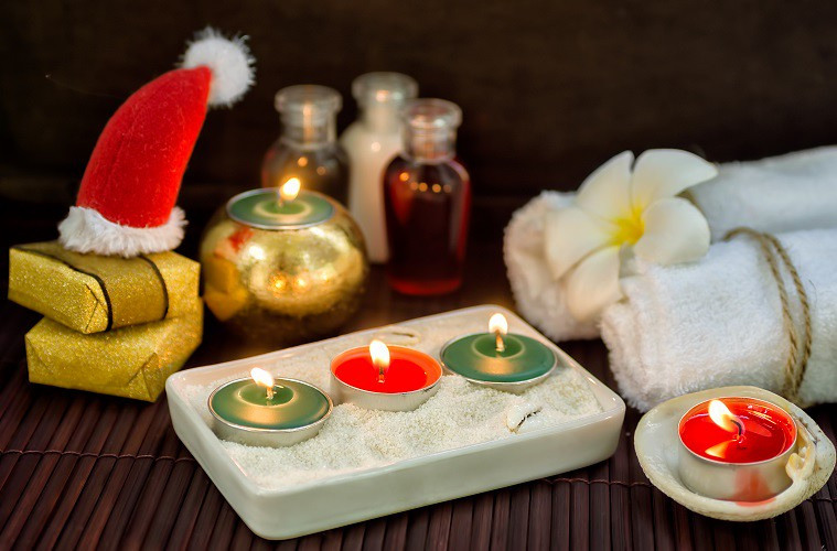 Dark christmas spa background with candles, presents and little Santa hat