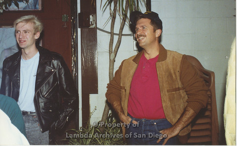 P001.152m.r.t 1st Anniversary 1991: Man in white shirt and black leather jacket next to man in red shirt and brown jacket